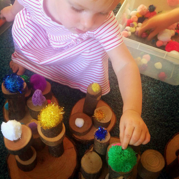 Simple toddler play ideas: Pom poms as loose parts for block play